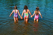 Alaska. Fairbanks. Three young girls hold hands as they wade into the Chena River. MR.