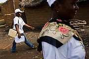A heath worker and a community volunteer walk through the village of Gidan-Turu, northern Ghana during a national polio immunization exercise on Thursday March 26, 2009..