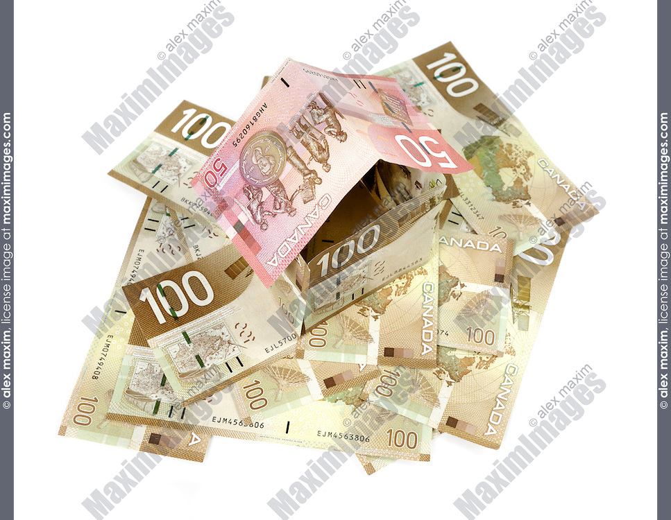 Model of a house made from Canadian dollar bills standing on a pile of money closeup Mortgage Investment Property insurance Property tax Banking concept Isolated silhouette on white