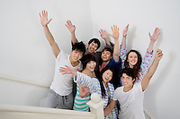 Group of young friends raising arms