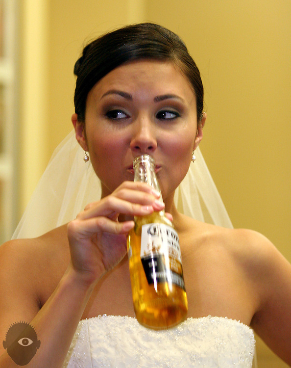 A bride enjoys a Corona to help take the edge off a bit as the ceremony time fast approaches.