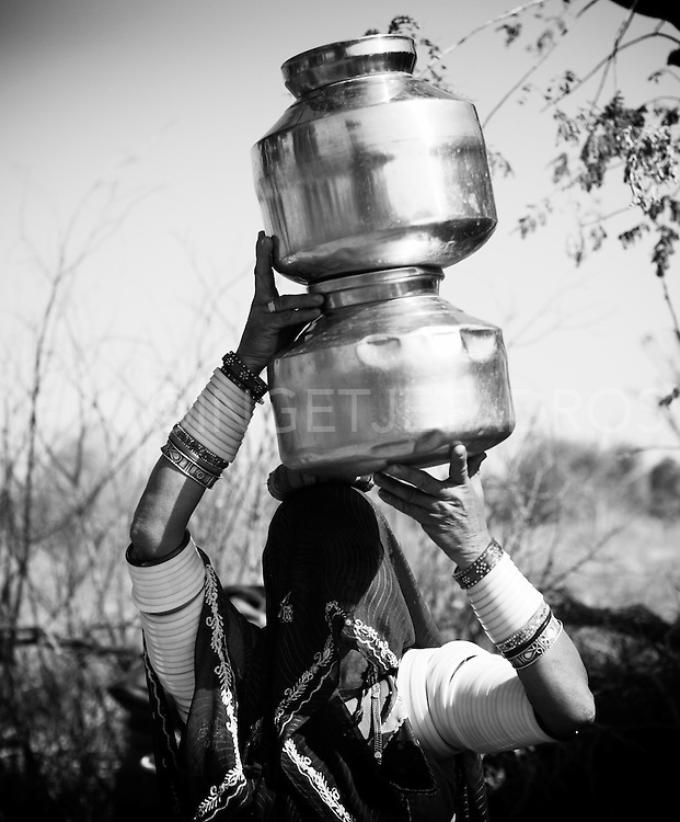 Rabari women work very hard to collect water.<br /> I was watching this women who was collecting water all afternoon and must have made at least 8 trips to the well with heavy pots full of water on her head.<br /> Southern Rajahstan, India 2012