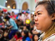 10 JANUARY 2015 - BANGKOK, THAILAND: A woman watches a television broadcast at Children's Day festivities in Bangkok. National Children's Day falls on the second Saturday of the year. Thai government agencies sponsor child friendly events and the military usually opens army bases to children, who come to play on tanks and artillery pieces. This year Thai Prime Minister General Prayuth Chan-ocha, hosted several events at Government House, the Prime Minister's office.    PHOTO BY JACK KURTZ