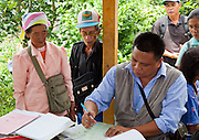 Villagers gather as a government official signs off thumbprints (due to illiteracy) of an elderly couple for the Malaysia census 2010 Nabalu, Sabah
