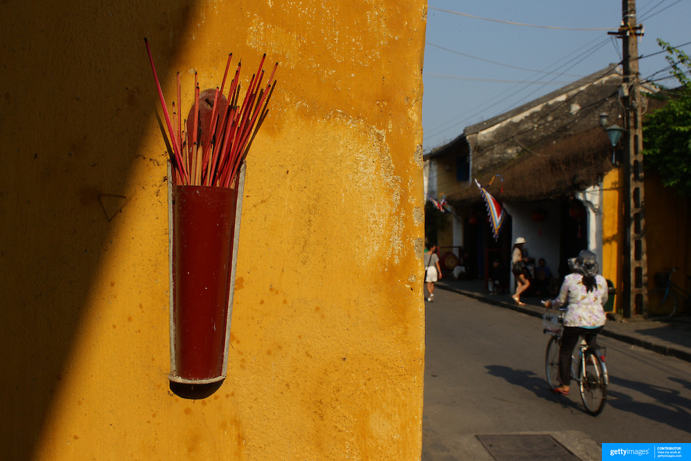 Joss sticks on a yellow wall in Hoi An, Vietnam. Hoi An is an ancient town and an exceptionally well-preserved example of a South-East Asian trading port dating from the 15th century. Hoi An is now a major tourist attraction because of its history. Hoi An, Vietnam. 5th March 2012. Photo Tim Clayton