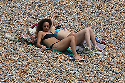 © Licensed to London News Pictures. 24/06/2014. Brighton, UK. Two woman on Brighton beach. Despite a cloudy day the weather is nice and warm with some people relaxing and sunbathing on the beach in Brighton. Photo credit : Hugo Michiels/LNP