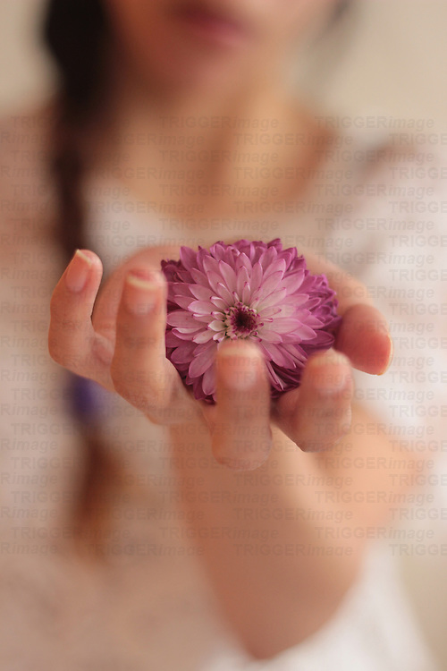 photograoh of a girl holding a purple flower in one hand