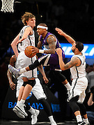 Sacramento Kings' Isaiah Thomas (22) leaps between Brooklyn Nets' Andrei Kirilenko (47) and Deron Williams (8) to pass the ball during an NBA basketball game on Sunday, March 9, 2014 at Barclays Center in New York. (AP Photo/Kathy Kmonicek)