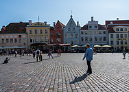 Tallinn, Estonia -- July 23, 2019. Pedestrians and tourists walk through a town square in Tallinn, Estonia with restaurants.