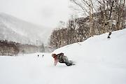 Alex Yoder cruising the resort with classic snowsurf style--waste no inch of snow. Niseko, Hokkaido, Japan.