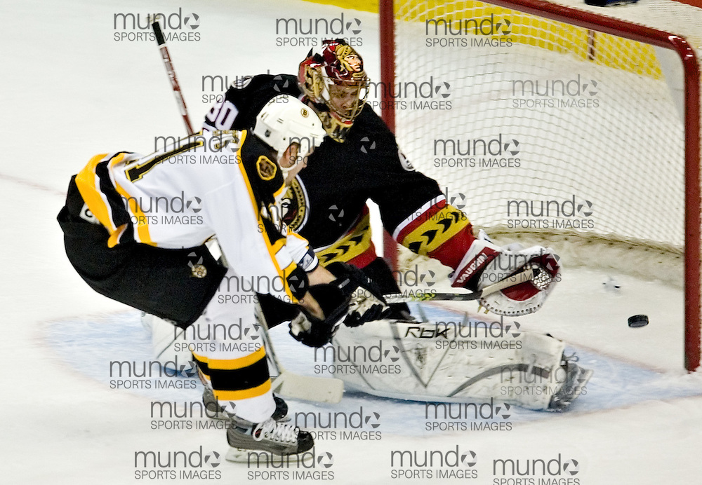 Andrew Alberts of the Boston Bruins(L) just misses the net as he breaks in alone on Ottawa Senators goaltender Mike Morrison in NHL action in Ottawa April 11, 2006..REUTERS/Geoff Robins<br />