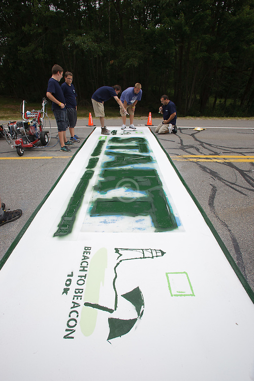 Ryan MacGillivrary oversees the painting of the official start line of Beach to Beacon 10K road race