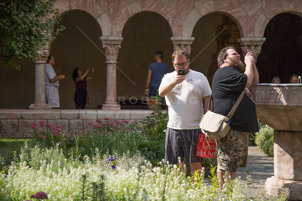 tourists taking photographs with their cellphones at The Cloisters in New York City