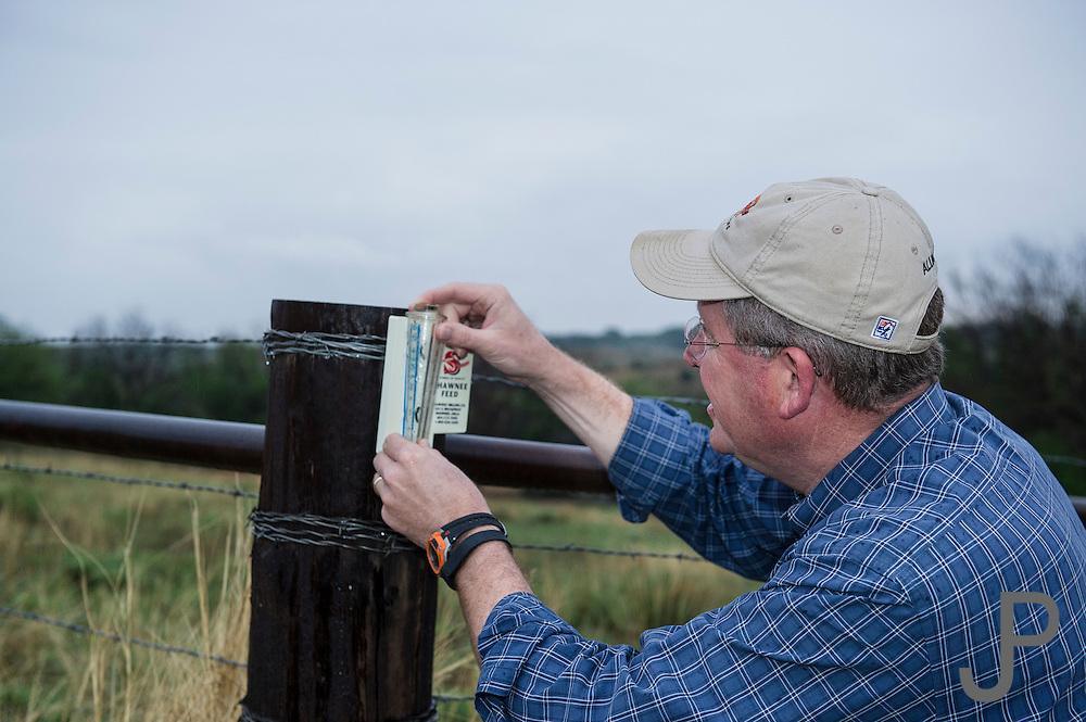Congressman and western Oklahoma rancher Frank Lucas checking the rain gauge at his farm near Cheyenne, Oklahoma
