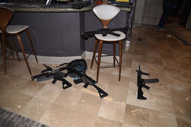 Investigators have released dramatic new photos of the Las Vegas hotel room from which Stephen Paddock murdered 58 people. Images show Paddock hid a camera in a food cart outside his room, as well as mounting one on the door's peephole, proving he was keeping an eye out for anyone trying to get into his room. There is a also a close up photo of the broken window through which he fired his assault rifles, which more images showing the guns and ammunition littered around his room. After unleashing a tirade of bullets on revelers at a music festival below, killing 58, Paddock committed suicide by shooting himself. The massacre, which happened on 17 October, 2017, is the deadliest mass shooting by a lone gunman in U.S. history. 23 Jan 2018 Pictured: View from sitting area towards the bar / kitchenette. Photo credit: LVMPD/ MEGA TheMegaAgency.com +1 888 505 6342