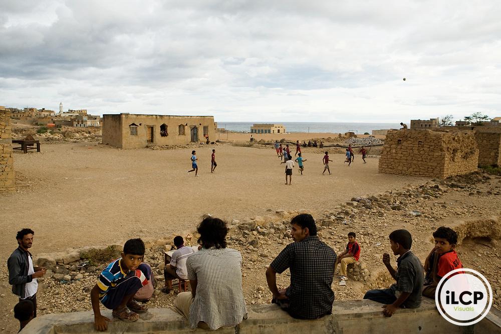 Soccer game played on rock field between buildings, Hawf Protected Area, Yemen