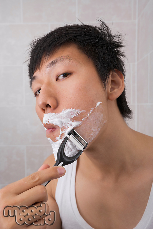 Portrait of mid adult Asian man shaving in bathroom