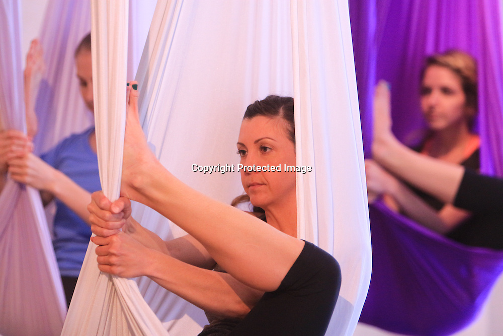 Lauren Casey, left, Melinda Finch, center, and Colleen Casey participate in an Aerial Yoga class at Salty Dog Yoga Sunday April 6, 2014 in Carolina Beach, N.C. (Jason A. Frizzelle)