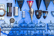 CHEFCHAOUEN, MOROCCO - 27th APRIL 2016 -  Mirrors, lamps and lanterns hang for sale on the blue walls of the Chefchaouen Medina - the blue city - Rif Mountains, Northern Morocco.