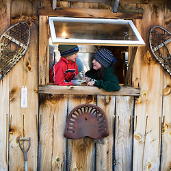 A brother and sister in the window of Fifield's Sugar House in Strafford, Vermont.