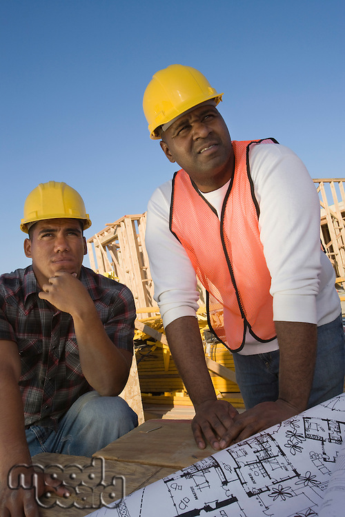 Two construction workers leaning to table with blueprints