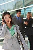 Businesswoman using mobile phone with colleagues in background, outdoors