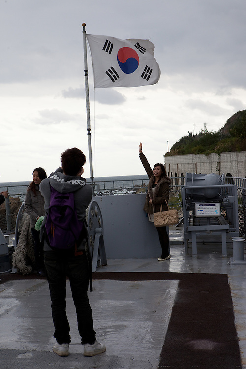 Korean tourists photographing themself on the top deck of the warship exhibited in the Unification Park / Jeongdongjin, South Korea, Republic of Korea, KOR, 07 October 2009.