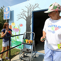 Kathryn Rhea, Director of Keep Tupelo Beautiful, Nettie Davis, Tupelo Ward 4 Councilwoman, work on painting a mural on the storm shelter on Front Street in Tupelo Wednesday. The project, started by Davis, is to beautify the shelter in conjunction with Keep Tupelo Beautiful.