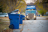 Domestic Waste collection and removal is part of everyday life in cities and towns across the nation. Household waste being collected curbside using mobile waste containers and hydraulic lifts front mounted on garbage truck.