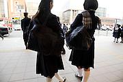two teenaged female Japanese students in school uniform waiting