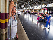 19 MARCH 2015 - BANGKOK, THAILAND:   A man prepares to step off the Ayutthaya to Bangkok third class train as the train pulls into Hua Lamphong, the main Bangkok train station. The train line from Bangkok to Ayutthaya was the first rail built in Thailand and was opened in 1892. The State Railways of Thailand (SRT), established in 1890, operates 4,043 kilometers of meter gauge track that reaches most parts of Thailand. Much of the track and many of the trains are poorly maintained and trains frequently run late. Accidents and mishaps are also commonplace. Successive governments, including the current military government, have promised to upgrade rail services. The military government has signed contracts with China to upgrade rail lines and bring high speed rail to Thailand. Japan has also expressed an interest in working on the Thai train system. Third class train travel is very inexpensive. Many lines are free for Thai citizens and even lines that aren't free are only a few Baht. Many third class tickets are under the equivalent of a dollar. Third class cars are not air-conditioned.        PHOTO BY JACK KURTZ