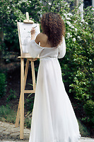 Beautiful woman sumi-e artist with an easel painting outdoors in a green garden in sunlight wearing a sheer white gown