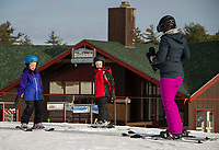 Ellianah Barton, Jackson Barton and Delia Grace boot up for their first runs of the season at Gunstock Mountain on Sunday morning.  (Karen Bobotas/for the Laconia Daily Sun)