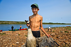 """Brendan Felix Head, 14, prepares to de-feather a duck in The Thelon, the largest and most remote game sanctuary in North America, which almost no one has heard of.  For the Akaitcho Dene, the Upper Thelon River is """"the place where God began.""""  Sparsely populated, today few make it into the Thelon. Distances are simply too far, modern vehicles too expensive and unreliable. For the Dene youth, faced with the pressures of a western world, the ties that bind the people and their way of life to the land are even more tenuous. Every impending mine, road, and dam construction threatens to sever these connections. In July and August, 2011 a group of youth paddled to their ancestral hunting ground and spiritual abode.  this next generation of young leaders will be the ones who will need to speak for the Thelon the loudest. (Photo by Ami Vitale)"""