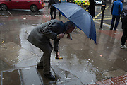 A man picks-up a dropped item as Storm Georgina sweeps across parts of Britain and in central London, lunchtime office workers were caught out by torrential rain and high winds, on 24th January 2018, in London, England. Pedestrians resorted to leaping across deep puddles at the junction of New Oxford Street and Kingsway at Holborn, the result of overflowing drains.