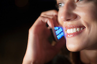 Woman smiles as she listens on mobile phone at night