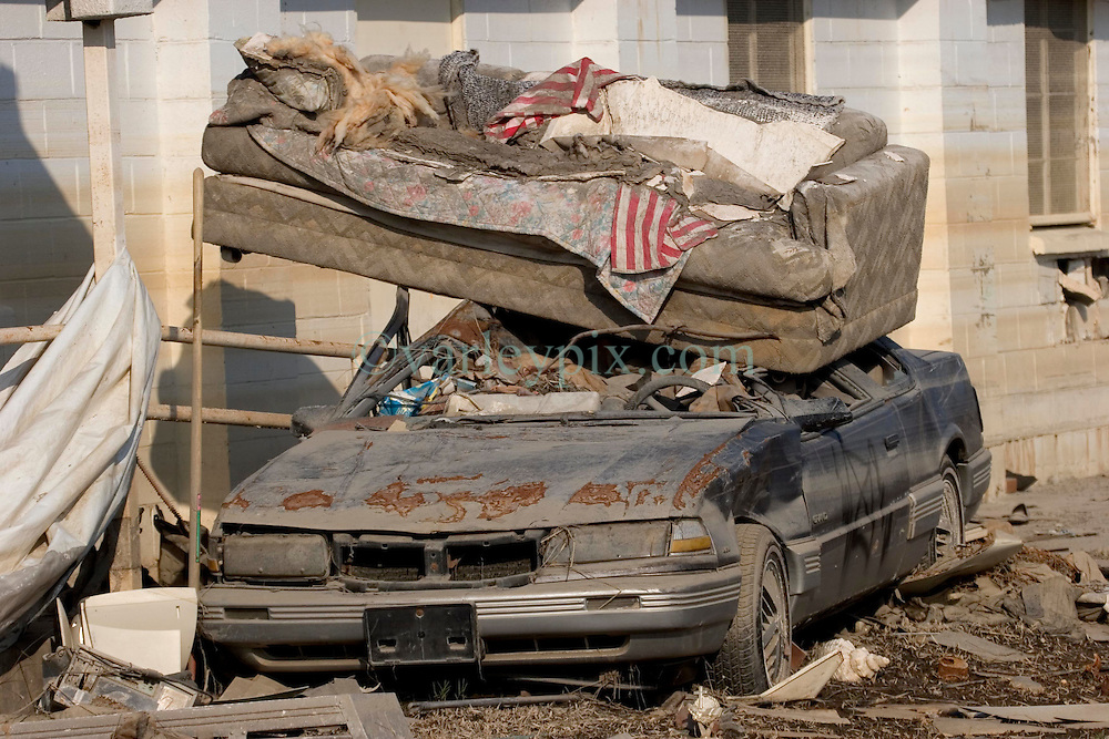 30 Sept, 2005.  New Orleans, Louisiana. Lower 9th ward. Hurricane Katrina aftermath. <br /> The remnants of the lives of ordinary folks, now covered in mud as the flood waters remain. A sofa lies where it came to rest on a car as the flood waters receded.<br /> Photo; ©Charlie Varley/varleypix.com