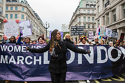 London, UK. 19th January, 2019. Dr Shola Mos-Shogbamimu leads thousands of women taking part in the Global Women's March from BBC Broadcasting House to Trafalgar Square to attend a Bread & Roses Rally Against Austerity organised by Women's March London. Inspired by the 1912 Bread & Roses protests which revolutionised workers' rights for women and in the light of Brexit, the organisers called for assurances from the Government in ending policies of austerity which lead to economic oppression, violence against women, the gender pay gap, racism, fascism, institutional sexual harassment and the hostile environment experienced by marginalised groups.