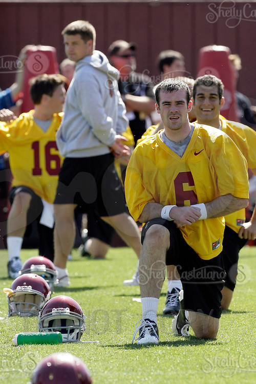 28 March 2009: 5 quarterbacks line up to stretch before the first day of '09 USC Trojans Pac-10 college football spring practice on campus in Southern California on a hot 81' sunny day.  #6 Chris McCaffery, #9 John Manooglan, #16 Mitch Mustain, #7 Matt Barkley, #15 Aaron Corp with coach Jeremy Bates walking through in the background.