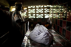 After the women finish to wash and dress Mommy's body the mosque morgue caretaker Kalil Conteh ties her body up.