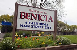 """Town welcome sign for Benicia, California.  Sign has colorful flowers planted underneath and reads """"A California Main Street City""""."""