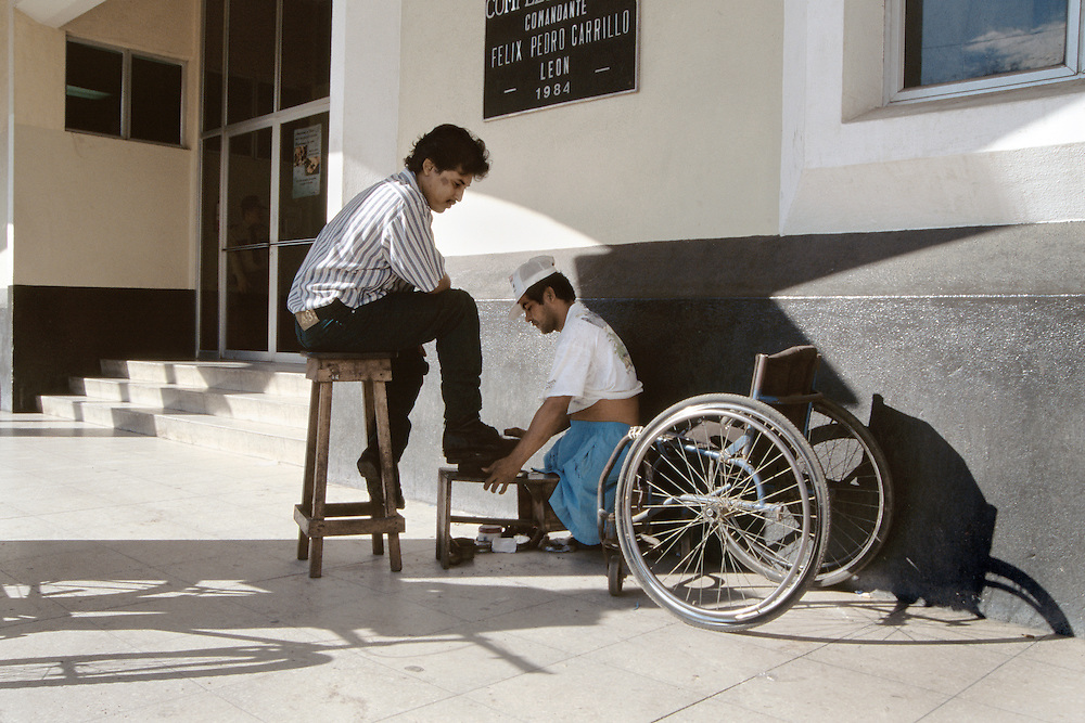 Manuel deJesus works shining shoes from his wheelchair in the streets of León, Nicaragua.