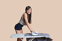 Portrait of a young woman ironing shirt over colored background