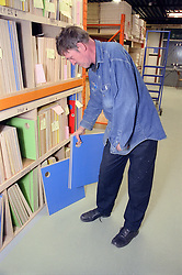 Man with disability selecting materials in warehouse,