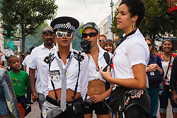 "London, August 24th 2014. ""Officers"" from the ""Soca Police"" ensure revellers keep dancing as thousands of Londoners of all races and cultures attend Notting Hill Carnival's ""Family friendly"" day ahead of the main carnival on August Bank Holiday Monday."