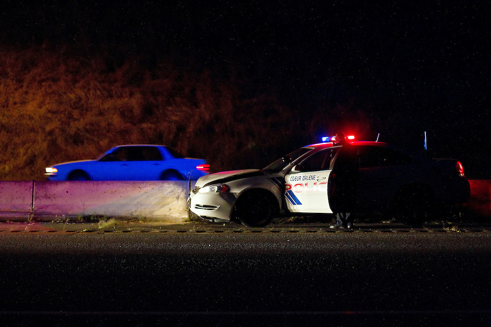 A Coeur d'Alene Police officer surveys the damage to a patrol car that was involved in an accident Sunday on the eastbound lanes of Interstate-90 near the 15th Street onramp. The officer crashed after trying to avoid an alleged drunk driver who was driving on the wrong side of the freeway around 9 p.m.