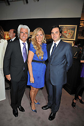 Left to right, ANTONIS LIBERIS, his wife ELENA MAKRI LIBERIS and EDUARDO SANCHEZ PEREZ at a party to celebrate the publication of Elena Makri Liberis's book 'Every Month, Same day' held at Sotheby's, 34-35 New Bond Street, London on 5th May 2009.