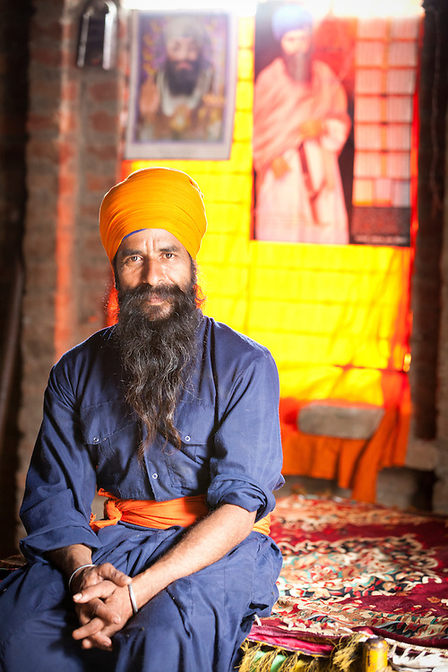 A Niahng SIkh posing for a picture at his home.The Nihangs are warrior sikhs and their attire consists of blue colo