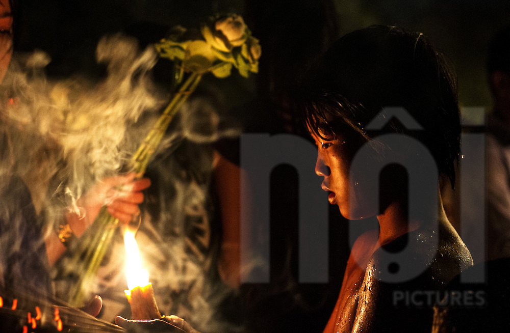 A young Khmer boy holds a candle for people to light their incense
