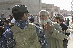 November 11, 2016 - Mosul, Nineveh, Iraq - 11/11/2016. Mosul, Iraq. A male resident of Mosul's Al Antisar district talks to an Iraqi Police officer, as locals queue for food handouts from local volunteers. The Al Intisar district was taken four days ago by Iraqi Security Forces (ISF) and, despite its proximity to ongoing fighting between ISF and ISIS militants, many residents still live in the settlement without regular power and water and with dwindling food supplies...The battle to retake Mosul, which fell June 2014, started on the 16th of October 2016 with Iraqi Security Forces eventually reaching the city on the 1st of November. Since then elements of the Iraq Army and Police have succeeded in pushing into the city and retaking several neighbourhoods allowing civilians living there to be evacuated - though many more remain trapped within Mosul. (Credit Image: © Matt Cetti-Roberts via ZUMA Wire)